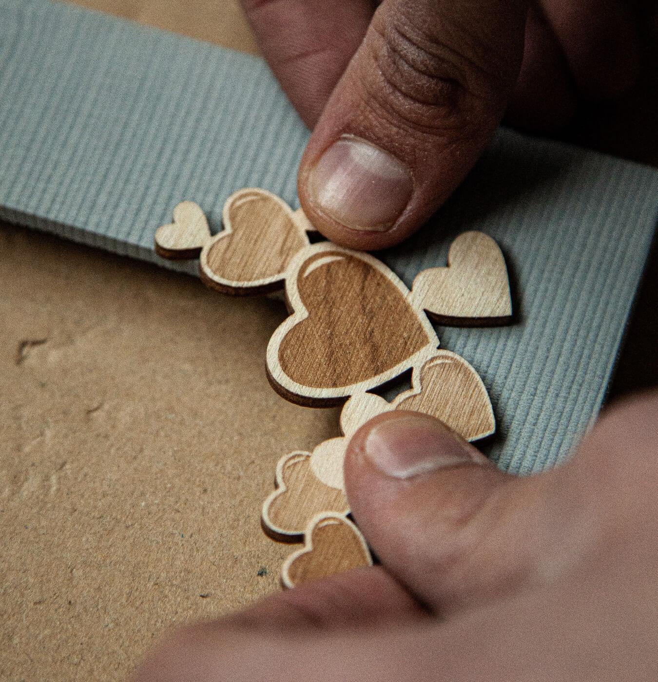 artigiano applica cuori su cornice portafoto